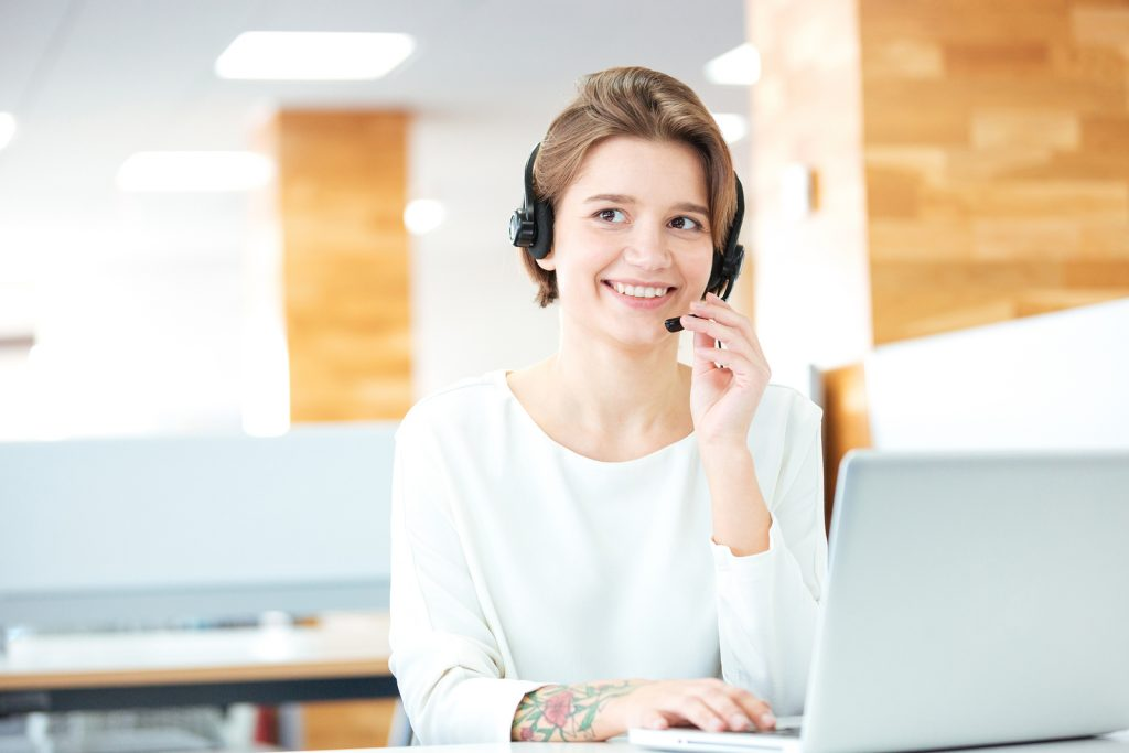 Cheerful attractive young woman sitting and working in call center